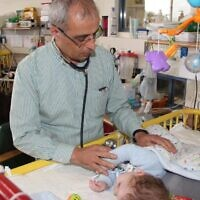 Dr. Eliezer Be'eri of the ALYN Hospital in Jerusalem treating a baby using the CoughSync medical device. (Courtesy of ALYN Hospital)