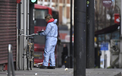A police forensic officer works at the scene of Sunday's terror stabbing attack in the Streatham area of south London Monday Feb. 3, 2020 (AP Photo/Alberto Pezzali)