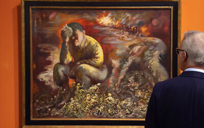 "A man looks at a 1944 painting ""Cain or Hitler in Hell,"" by George Grosz, during a press preview at the German Historical Museum in Berlin, Germany, February 4, 2020. (AP Photo/Jens Meyer)"