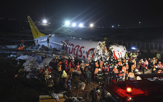 Rescue members and firefighters work around the wreckage of a plane after it skidded off the runway at Istanbul's Sabiha Gokcen Airport, in Istanbul, February 5, 2020. (Ismail Coskun/IHA via AP)