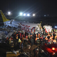 Rescue members and firefighters work around the wreckage of a plane after it skidded off the runway at Istanbul's Sabiha Gokcen Airport, in Istanbul, Wednesday, Feb. 5, 2020. A plane skidded off the runway Wednesday at Istanbul's Sabiha Gokcen Airport, crashing into a field and breaking into pieces. Passengers were seen evacuating through cracks in the plane and authorities said dozens have been injured. (Ismail Coskun/IHA via AP)