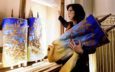 In this February 1, 2020, photo, Rabbi Jacqueline Mates-Muchin removes a Torah scroll from the ark, a cabinet that houses scrolls of the Hebrew Bible, while preparing for Shabbat morning service at Temple Sinai in Oakland, California (AP/Noah Berger)