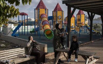 In this Thursday, Feb. 6, 2020, photo, Israeli Arabs enjoy the day at a playground in the Israeli Arab town Kafr Qasim (AP Photo/Oded Balilty)