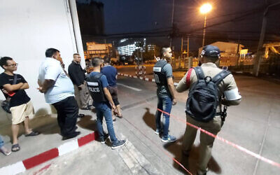 Police and bystanders stand near the scene of a shooting at the Terminal 21 mall, in Korat, Thailand,  Saturday, Feb. 8, 2020. (AP Photo)