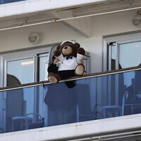 A woman holds a teddy bear on the balcony of the Diamond Princess cruise ship docked in the Yokohama Port in Yokohama, near Tokyo, February 11, 2020. (Jae C. Hong/AP)