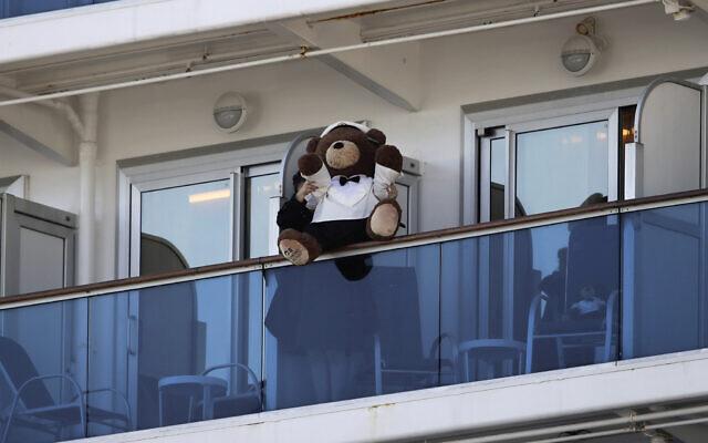 A woman holds a teddy bear on the balcony of the Diamond Princess cruise ship docked in the Yokohama Port in Yokohama, near Tokyo, February 11, 2020. (Jae C. Hong/AP)