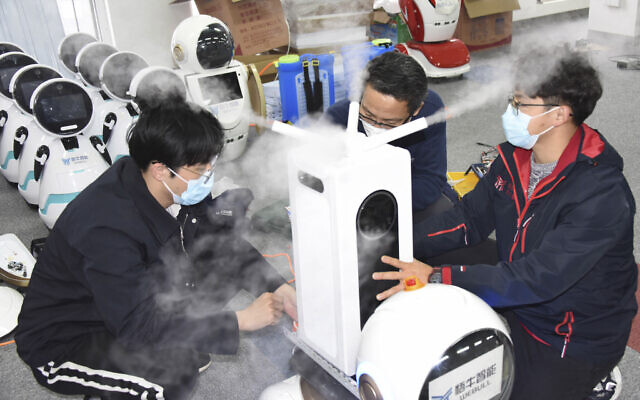 In this photo released by Xinhua News Agency, technicians work on a second generation disinfection robot in a technological company in Qingdao, eastern China's Shandong Province on February 11, 2020. (Li Ziheng/Xinhua via AP)