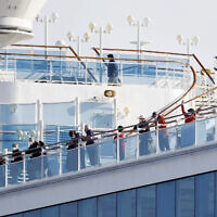 Passengers stand on the deck of the Diamond Princess cruise ship anchored at Yokohama Port in Yokohama, near Tokyo, February 12, 2020. (Yuta Omori/Kyodo News via AP)