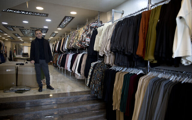 Palestinian shopkeeper Bilal Dwaik poses for a photo in his store, which sells clothes he imports from China, in the West Bank city Hebron,  February 12, 2020. (Majdi Mohammed/AP)