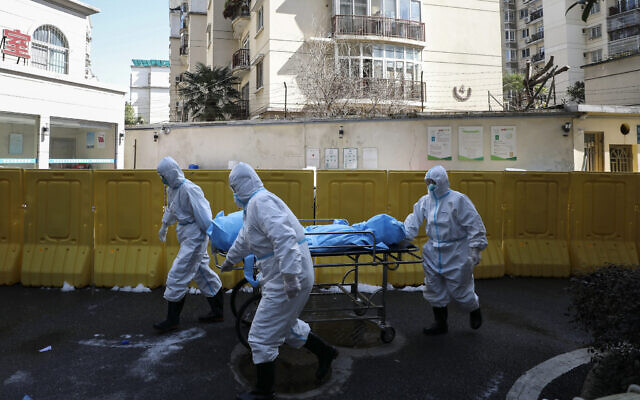 In this Sunday, Feb. 16, 2020, photo, medical workers move a person who died from COVID-19 at a hospital in Wuhan in central China's Hubei province. (Chinatopix via AP)