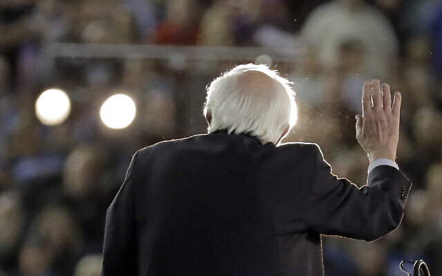 US Democratic presidential candidate Sen. Bernie Sanders Independent-Vermont, is lit by spotlights as he speaks at a campaign event in Tacoma, Washington, February 17, 2020. (Ted S. Warren/AP)