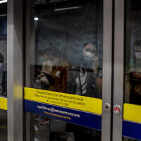 Commuters wearing face masks are mirrored in a subway station in Bangkok, Thailand, February 19, 2020. (AP Photo/Gemunu Amarasinghe)