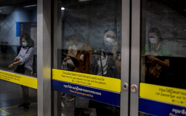 Commuters wearing face masks are mirrored in a subway station Bangkok, Thailand, February 19, 2020. (AP Photo/Gemunu Amarasinghe)