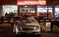 A car with covered dead bodies stands in front of a bar in Hanua, Germany Thursday, Feb. 20, 2020. German police say several people were shot to death in the city of Hanau on Wednesday evening. (AP Photo/Michael Probst)