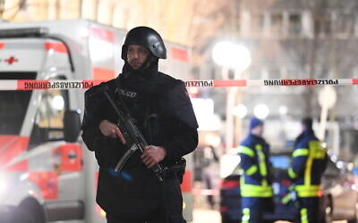 A police officer stands guard near the scene in front of a restaurant after a shooting in central Hanau, Germany, February 20, 2020. Eight people were killed in shootings in the German city of Hanau the previous evening, authorities said. (Boris Roessler/dpa via AP)