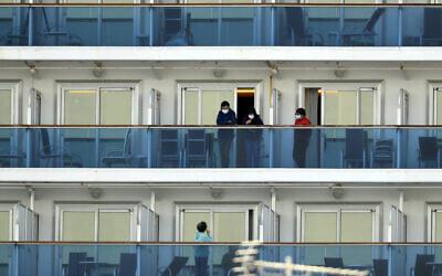 Passengers speak on balconies of the quarantined Diamond Princess cruise ship docked at a port in Yokohama, near Tokyo, February 20, 2020. (Eugene Hoshiko/AP)