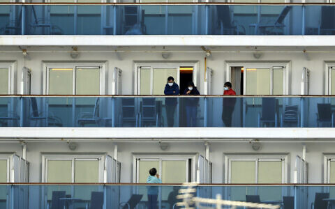 Passengers speak on balconies of the quarantined Diamond Princess cruise ship docked at a port in Yokohama, near Tokyo, February 20, 2020. (Eugene Hoshiko/AP)