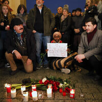 People attend a vigil for victims of a shooting in the central German town Hanau, in front of the Brandenburg Gate in Berlin, Germany, Thursday, Feb. 20, 2020 (AP Photo/Markus Schreiber)