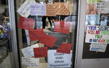 This Nov. 21, 2019 file photo shows signs posted on windows and doors at Syracuse University displaying anti-racism expressions in Syracuse, NY (AP Photo/Carolyn Thompson, File)