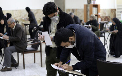 Voters with face masks fill out their ballots in the parliamentary elections at a polling station in Tehran, Iran, February 21, 2020. (AP Photo/Vahid Salemi)