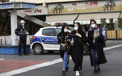 A policeman and pedestrians wear masks to help guard against the coronavirus, in downtown Tehran, Iran, February 23, 2020.(Ebrahim Noroozi/AP)