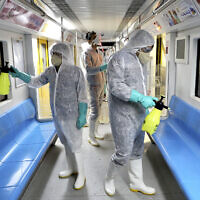 Workers disinfect subway trains against coronavirus in Tehran, Iran, in the early morning of Wednesday, February 26, 2020. (AP Photo/Ebrahim Noroozi)