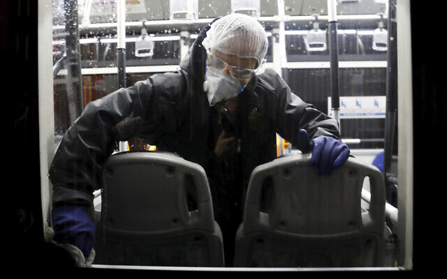 A worker disinfects a public bus against coronavirus in Tehran, Iran, in early morning of Wednesday, February 26, 2020. (AP Photo/Ebrahim Noroozi)