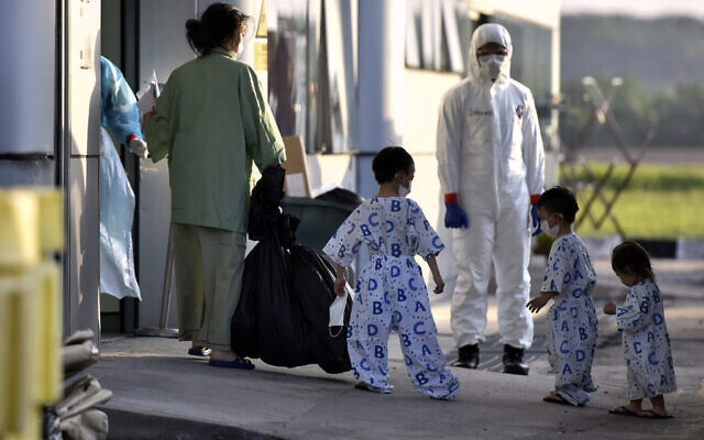 In this photo taken and released by Malaysia's Ministry of Health, a health worker looks at a woman and children arrive at Kuala Lumpur International Airport in Sepang, Malaysia, Wednesday, Feb. 26, 2020, after being evacuated from China's Wuhan, the epicenter of the coronavirus outbreak. (Muzzafar Kasim/Malaysia's Ministry of Health via AP)