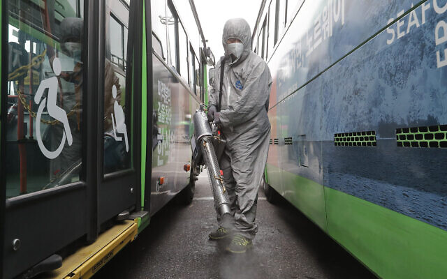 A worker wearing a protective suit sprays disinfectant as a precaution against the coronavirus at a bus garage in Seoul, South Korea, Wednesday, Feb. 26, 2020. (AP Photo/Ahn Young-joon)