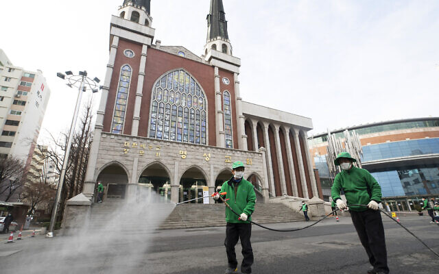 Workers wearing face masks spray disinfectant as a precaution against the new coronavirus in front of Myungsung Church in Seoul, South Korea, Wednesday, Feb. 26, 2020. (Yun Dong-jin/Yonhap via AP)