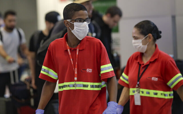 Airport employees wear masks as a precaution against the spread of the new coronavirus as they work at the Sao Paulo International Airport in Sao Paulo, Brazil, Wednesday, Feb. 26, 2020. (AP Photo/Andre Penner)
