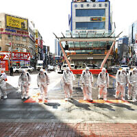 South Korean army soldiers wearing protective suits spray disinfectant to prevent the spread of the COVID-19 virus on a street in Daegu, South Korea, Feb. 27, 2020 (Lee Moo-ryul/Newsis via AP)