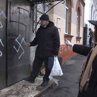 Illustrative: In this March 2, 2007 file photo, head of the Jewish community Gennady Klebanov, left, is about to enter the swastika-smeared door of the synagogue, as chief rabbi of Vladivostok Isroel Silberstain, right, points in the Russian Far Eastern Port of Vladivostok. (AP)