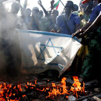 Sudanese students burn an Israeli flag as they demonstrate against the Israeli airstrikes in Gaza  outside the UN headquarters in Khartoum, Sudan, December 29, 2008.(AP/Abd Raouf)
