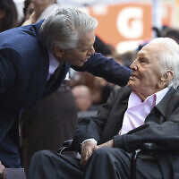 Honoree Michael Douglas, left, speaks with his father Kirk Douglas before a Hollywood Walk of Fame star ceremony on Nov. 6, 2018, in Los Angeles. (Chris Pizzello/Invision/AP)