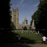 People sit in the sun in Victoria Tower Gardens backdropped by the Houses of Parliament in London, August 28, 2019. (Matt Dunham/AP)
