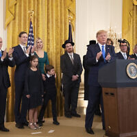 US President Donald Trump with, first lady Melania Trump, Vice President Mike Pence, from left, Jared Kushner and Ivanka Trump and their children Arabella Kushner and Joseph Kushner, applaud during a Hanukkah reception in the East Room of the White House on December 11, 2019, in Washington. (AP/Manuel Balce Ceneta)