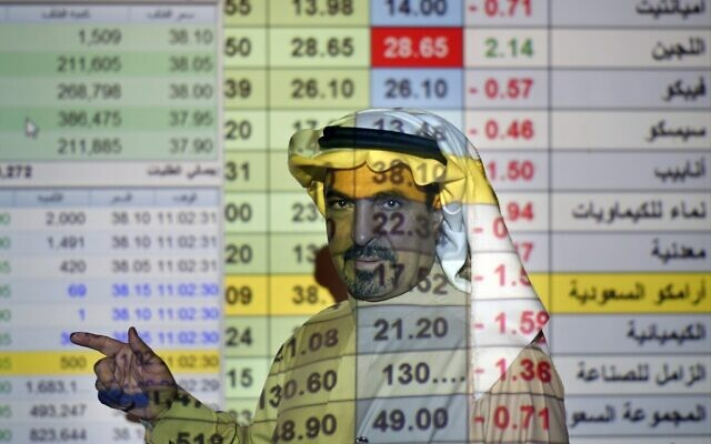 A trader talks to others in front of a screen displaying Saudi stock market values at the Arab National Bank in Riyadh, Saudi Arabia,  December 12, 2019. (Amr Nabil/AP)