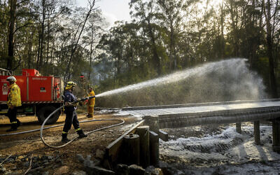 A firefighter coats a bridge with foam as a bushfire burns near Moruya New South Wales Australia