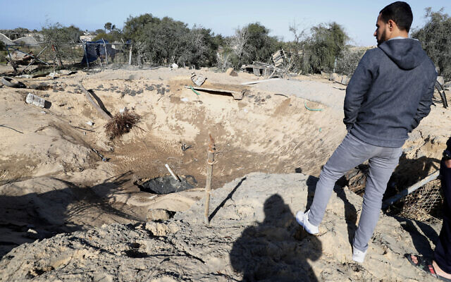 A resident inspects a crater following overnight Israeli missile strikes, in Rafah, southern Gaza Strip, Friday, Jan. 31, 2020.  (AP/Adel Hana)