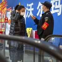 A security guard takes a customer's temperature at the entrance to a grocery store in Beijing, February 1, 2020. (AP Photo/Mark Schiefelbein)
