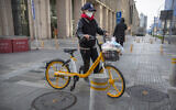 A woman wears a face mask as she pushes a bicycle along a street in Beijing, Saturday, Feb. 1, 2020.  (AP/Mark Schiefelbein)