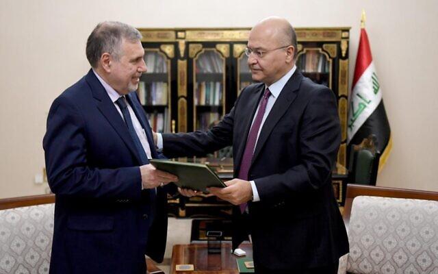 Iraqi President Barham Salih, right, instructs newly appointed Prime Minister Mohammed Allawi in Baghdad, Iraq, Saturday, Feb. 1, 2020. (Iraqi Presidency Media Office, via AP)