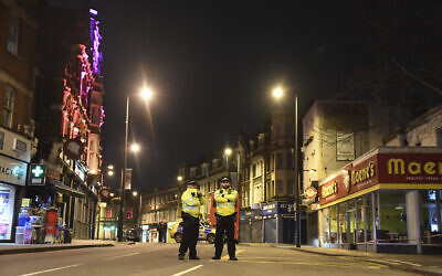 Police officers stand guard near the scene after a stabbing incident in Streatham, London, England, February 2, 2020. (AP Photo/Alberto Pezzali)