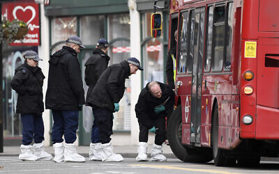 Police officers look under a bus as they work at the scene the day after a terror stabbing attack in the Streatham area of south London, February 3, 2020. (Alberto Pezzali/AP)
