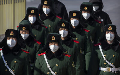 Paramilitary policemen wear face masks as they march in formation into a pedestrian underpass next to Tiananmen Square in Beijing, February 4, 2020. (Mark Schiefelbein/AP)