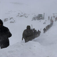 Emergency service members work in the snow around overturned vehicles, near the town of Bahcesehir, in Van province, eastern Turkey on February 5, 2020. (Yilmaz Sonmez/IHA via AP)