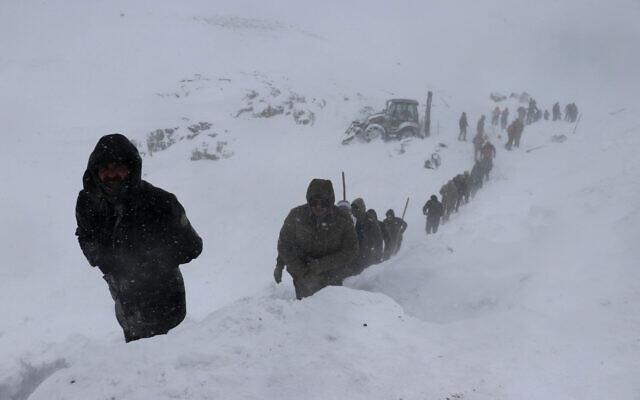 Emergency service members work in the snow around overturned vehicles, near the town of Bahcesehir, in Van province, eastern Turkey on February 5, 2020. (Yilmaz Sonmez/IHA via AP)