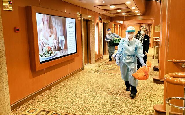In this February 4, 2020, photo taken by a passenger, medical workers in protective suits walk on the cruise ship Diamond Princess anchored off Yokohama, south of Tokyo (@daxa_tw via AP)