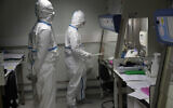 French lab scientists in hazmat gear inserting liquid in test tube manipulate potentially infected patient samples at Pasteur Institute in Paris, Feb. 6, 2020 (AP Photo/Francois Mori)